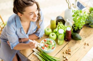 A smiling woman sitting down to eat a healthy green salad.