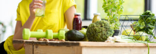 Green vegetables, nuts and fruit smoothies spread across a kitchen table.