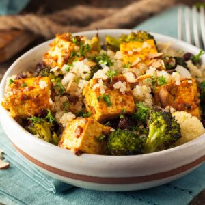 A nutritious bowl complete with roasted broccoli and colliflower, spiced tofu and shaved almonds atop a bed of golden quinoa.
