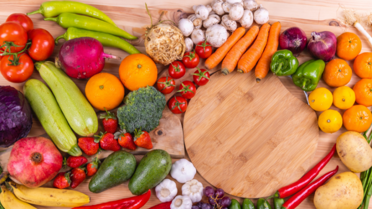Wood table with wood cutting board surrounded by vibrant fruits and vegetables.