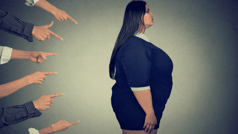 Fingers pointing at woman in larger body.